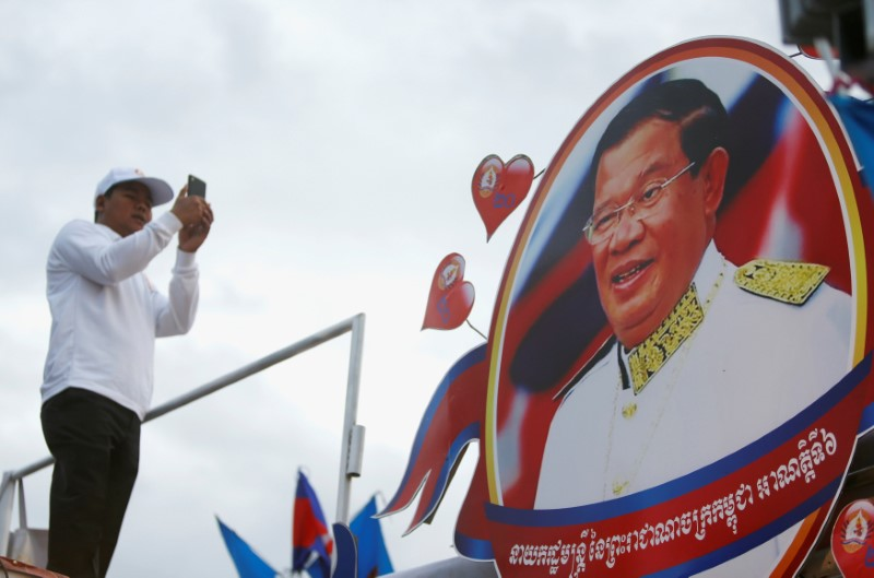 A supporter of the ruling Cambodian People's Party (CPP) uses a mobile phone to photograph a portrait of CPP president Hun Sen during an election campaign in Phnom Penh
