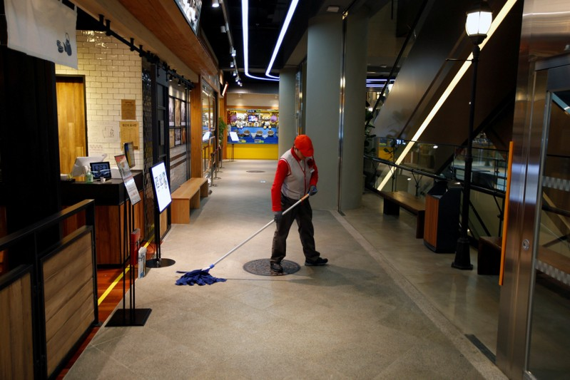 FILE PHOTO: A worker mops the floor at Lotte World Mall in Seoul