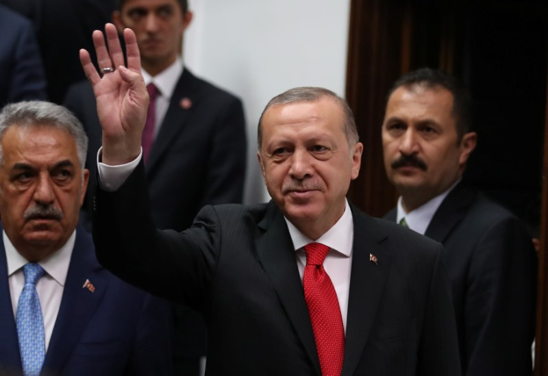 Turkish President Tayyip Erdogan greets members of parliament from his ruling AK Party as he arrives at the Turkish parliament in Ankara