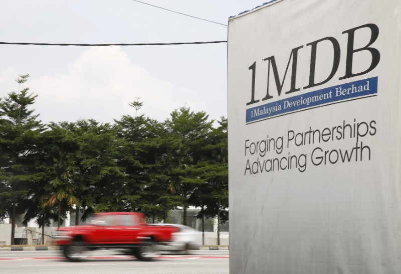 FILE PHOTO: Traffic passes a 1MDB billboard at the Tun Razak Exchange development in Kuala Lumpur