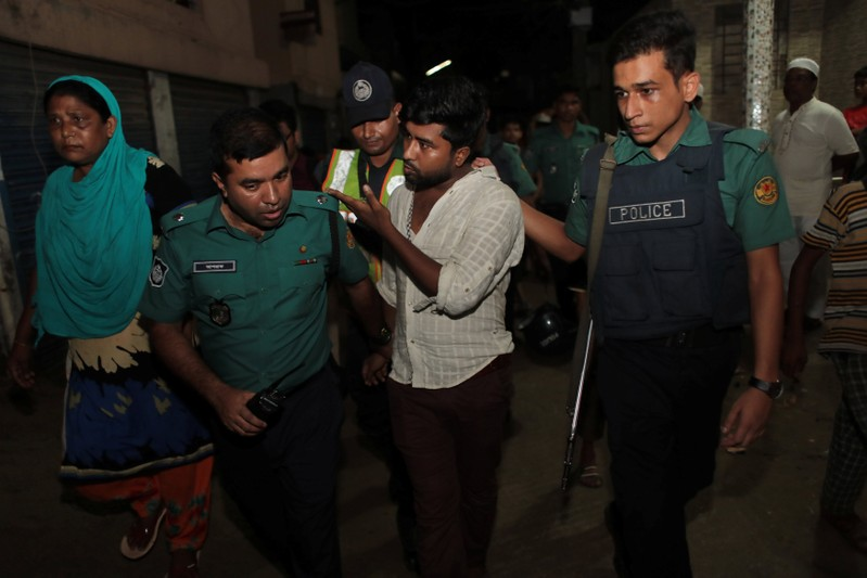 Police detain a man, brother of an alleged drug dealer Farhad Hossain Babu, during an anti drug raid in Dhaka