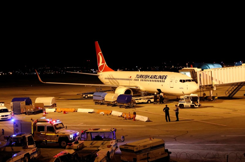 Firemen are seen entering the cargo compartment of a Turkish Airlines flight parked on the tarmac of Budapest Airport