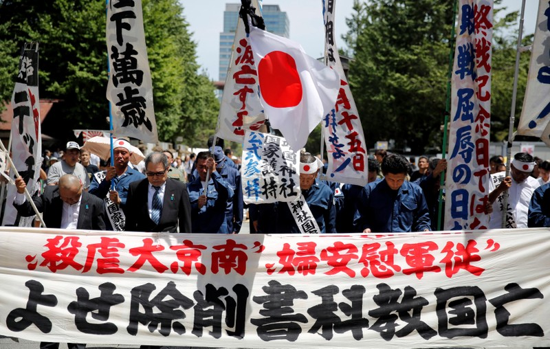 Members of a right wing group pay a silent tribute to the war dead at noon in front of Yasukuni Shrine in Tokyo