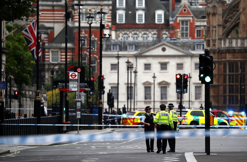 Police stand in the street after a car crashed outside the Houses of Parliament in Westminster, London