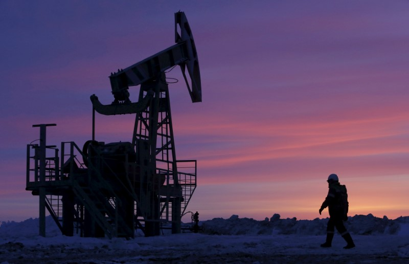 FILE PHOTO: File photo of a worker walking past a pump jack on an oil field owned by Bashneft, Bashkortostan