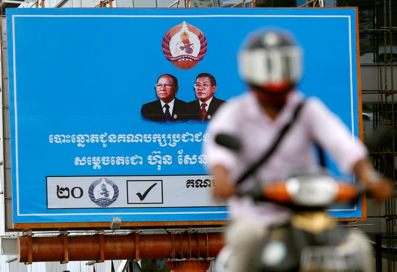 A man rides a motorcycle as a poster of the Cambodian People's Party (CPP) is seen at Koh Pich island in Phnom Penh
