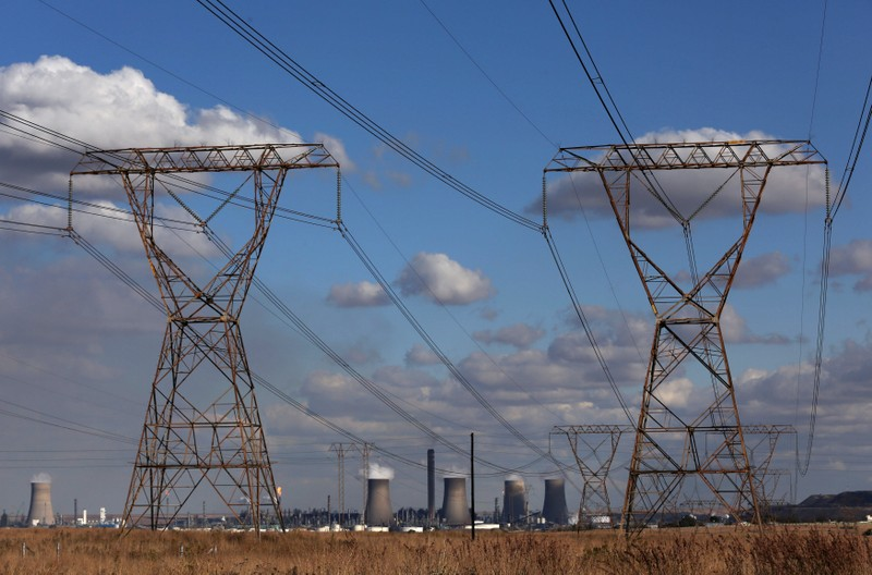 FILE PHOTO: Electricity pylons are seen near cooling towers of South African petrochemical company Sasol's synthetic fuel plant in Secunda, north of Johannesburg