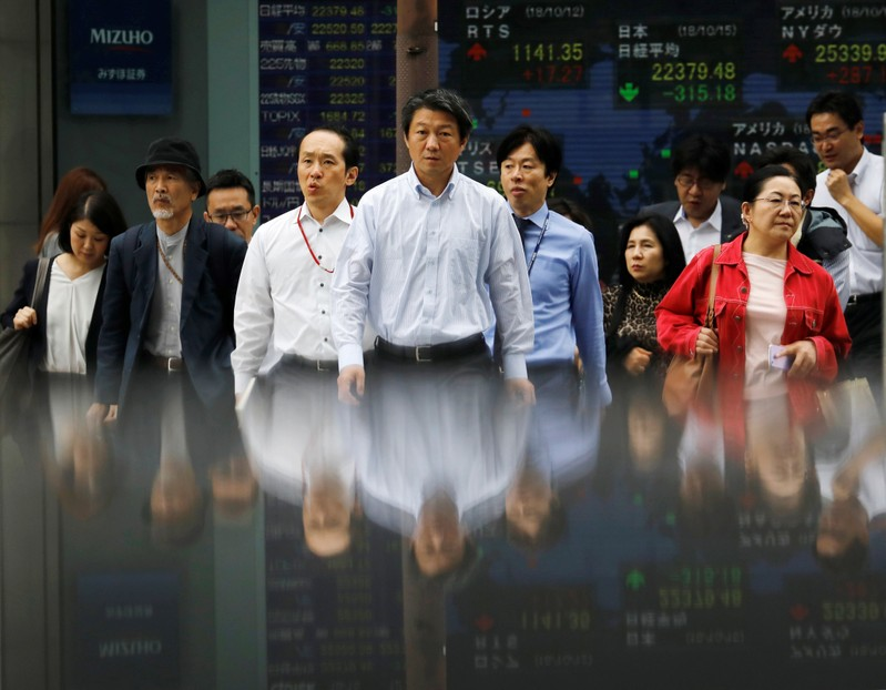 People walk in front of an electronic stock quotation board outside a brokerage in Tokyo