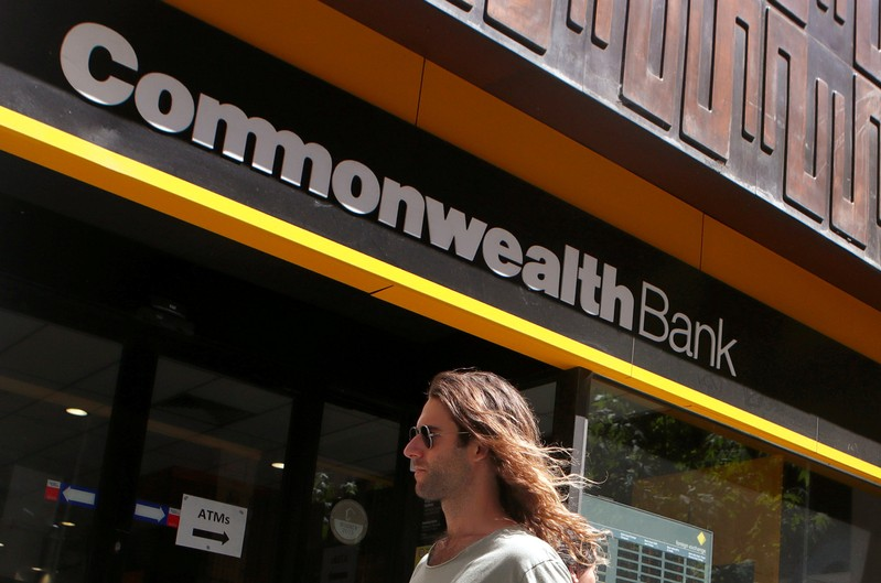 FILE PHOTO: A man uses his mobile phone as he leaves the Commonwealth Bank of Australia building in central Sydney