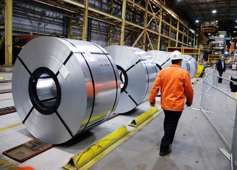 A worker walks by rolled up steel sits in the ArcelorMittal Dofasco steel plant in Hamilton, Ontario