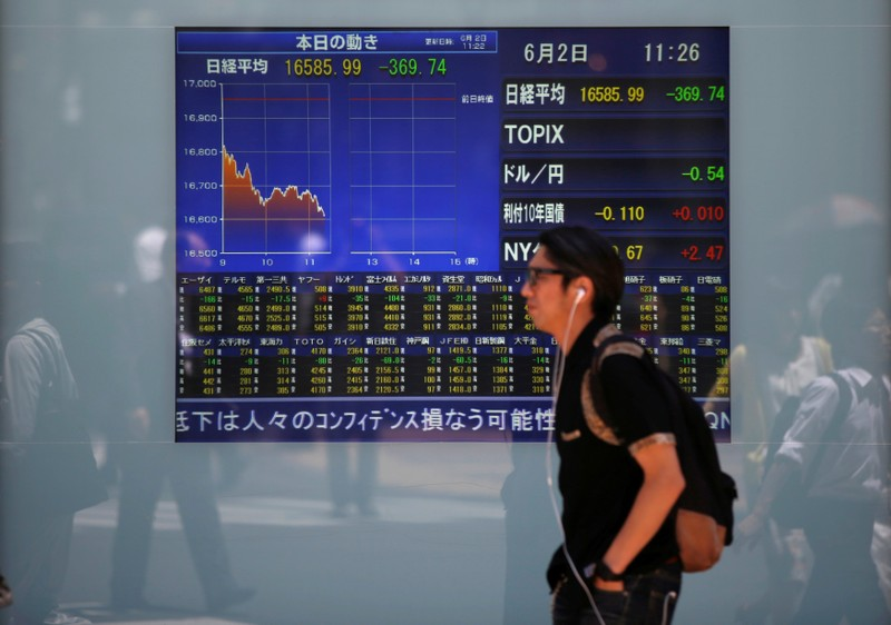 A man walks in front of a screen showing today's movements of Nikkei share average outside a brokerage in Tokyo, Japan