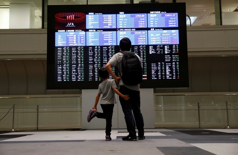 Visitors look at a stock quotation board at Tokyo Stock Exchange in Tokyo
