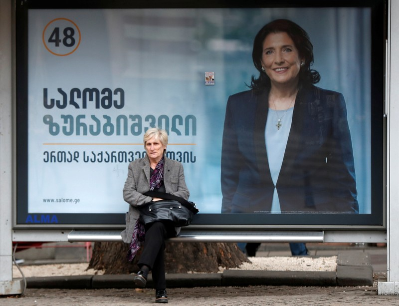 A woman sits at a bus stop decorated with a campaign poster of pro-government presidential candidate Salome Zurabishvili in Tbilisi
