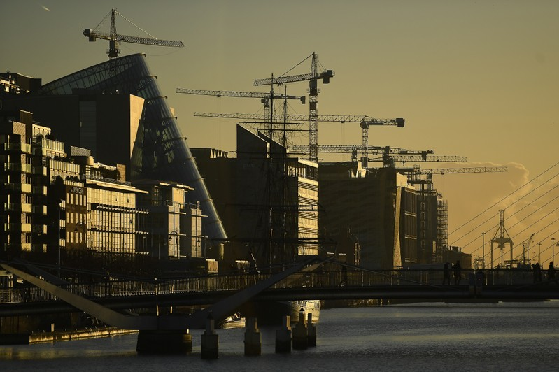 Construction cranes are seen at sunrise in the financial district of Dublin
