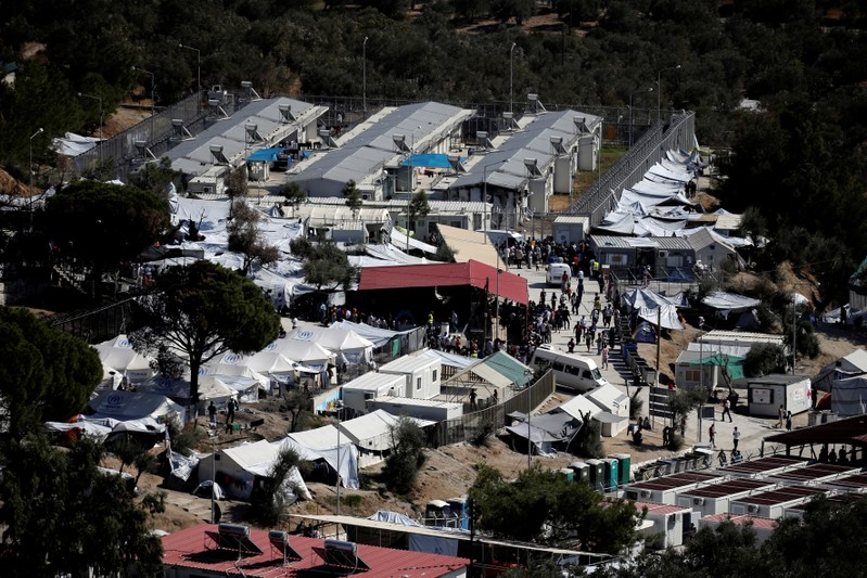 FILE PHOTO: People make their way inside the Moria migrant camp on the island of Lesbos
