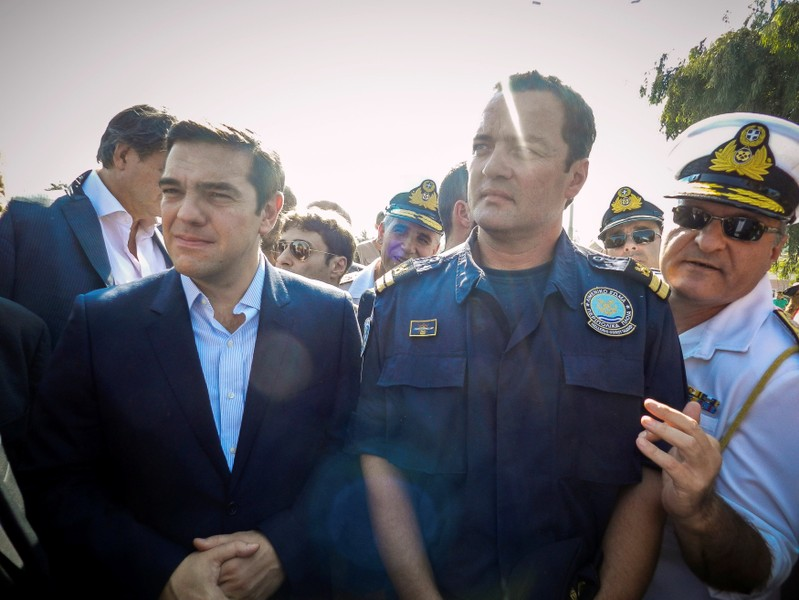 FILE PHOTO: Greek Coast Guard Lieutenant Kyriakos Papadopoulos stands next to Greek Prime Minister Alexis Tsipras during Tsipras's visit to the island of Lesbos