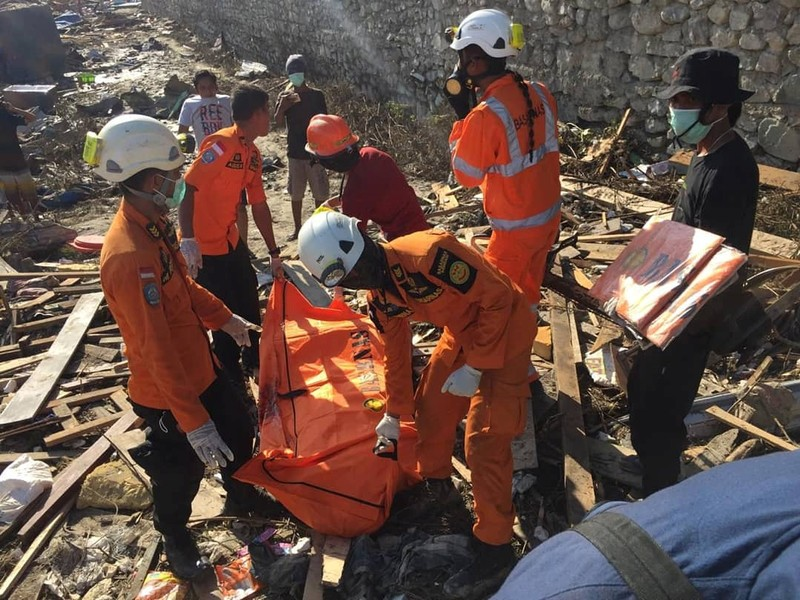 Humas Basarnas personnel carry a recovered body in Palu