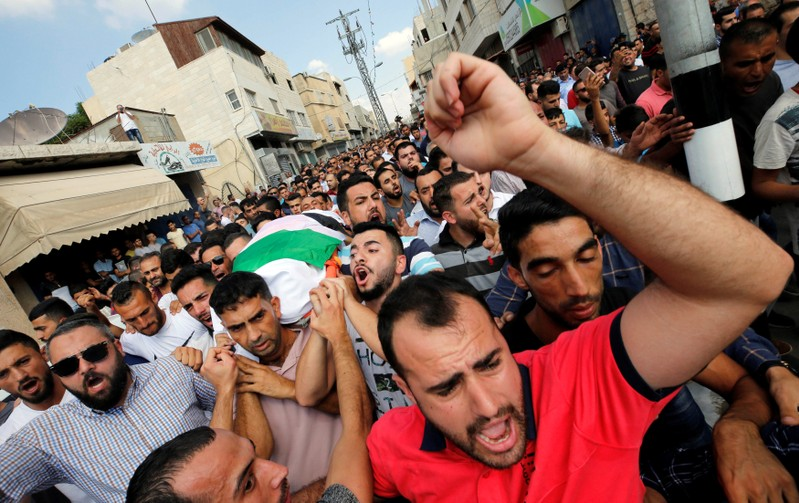 Mourners carry the body of Palestinian woman Aisha al-Rawbi during her funeral in the town of Biddya near Nablus in the occupied West Bank