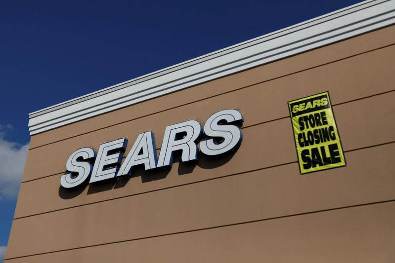 A store closing sale sign is posted next to a Sears logo in New Hyde Park, New York