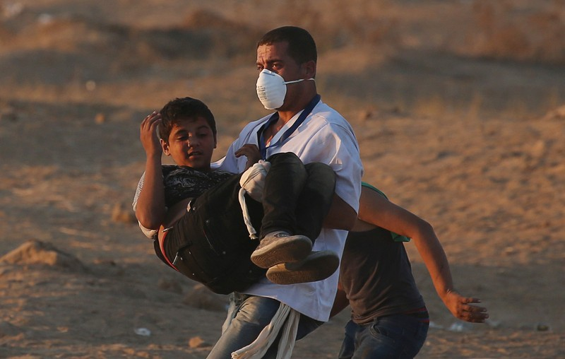 Wounded Palestinian boy is evacuted during a protest at the Israel-Gaza border fence in the southern Gaza Strip