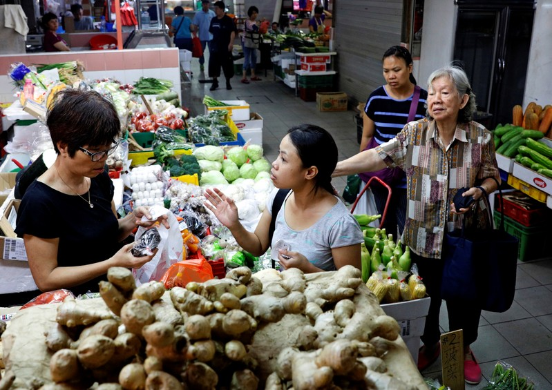 FILE PHOTO: People shop for vegetables at a wet market in Singapore