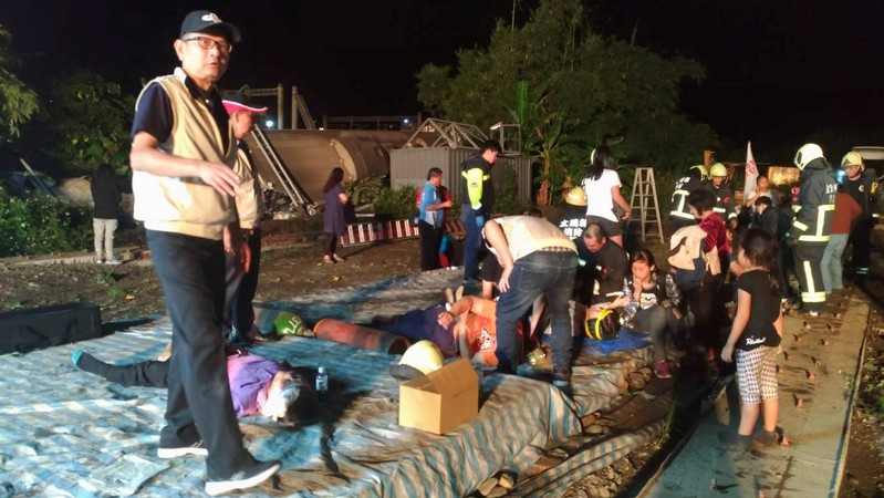 Rescuers tend to injured passengers after a train derailed in Yilan