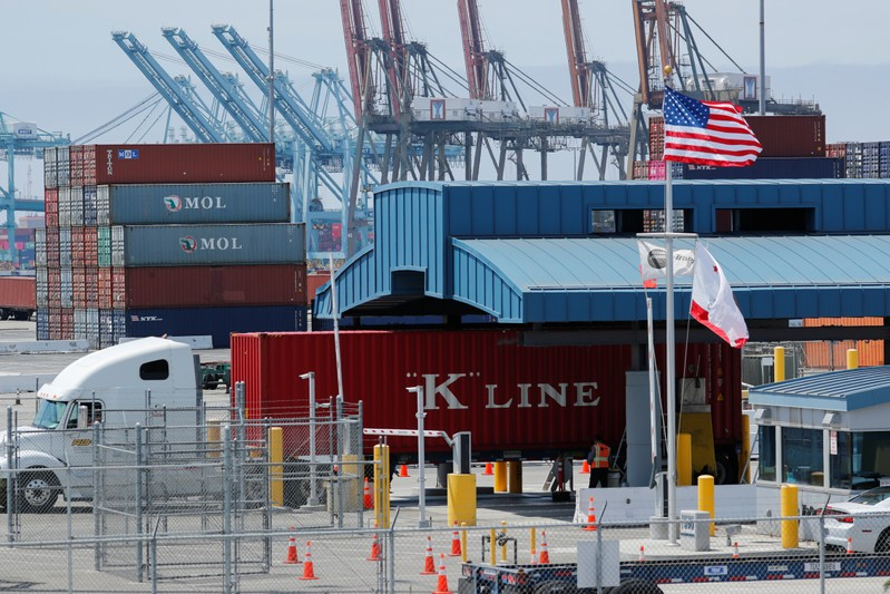 Trucks offload containers from ship at the port of Los Angeles in Los Angeles, California