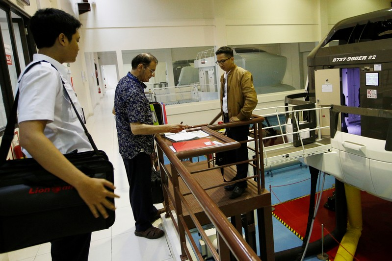 A senior instructor of Lion Air Group writes in a report book after a Jet Introduction session in Boeing 737-900ER simulator at Angkasa Training Center near Jakarta