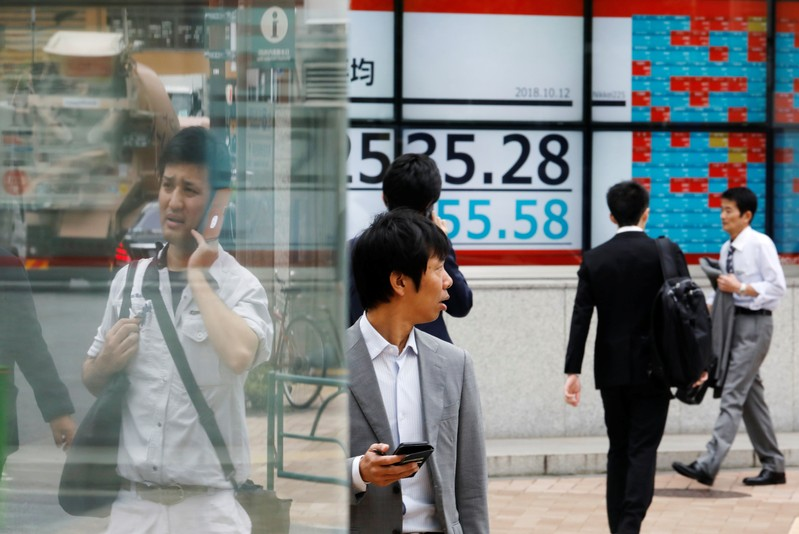 FILE PHOTO - People walk past an electronic board showing Japan's Nikkei average outside a brokerage in Tokyo