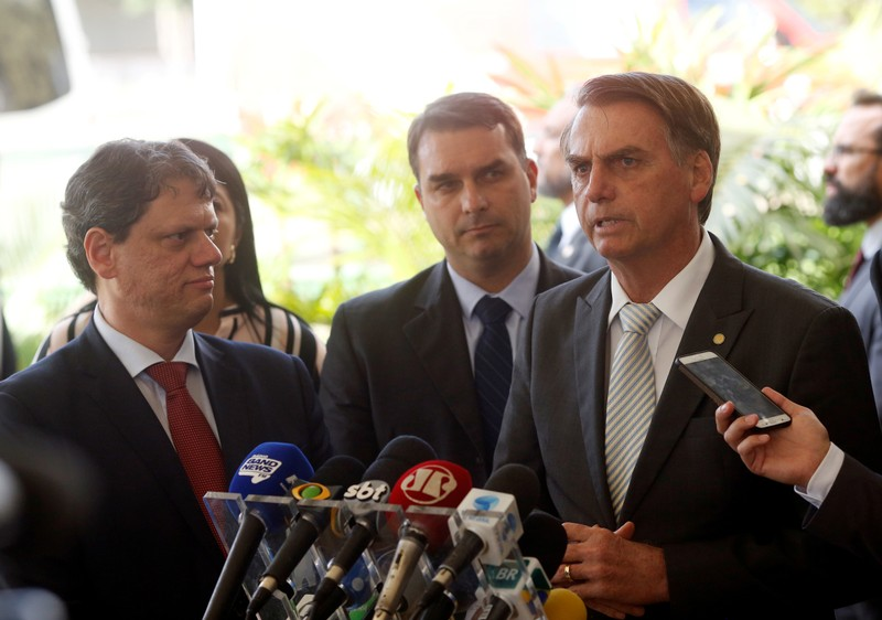 Brazil's President-elect Jair Bolsonaro speaks near his son Flavio Bolsonaro and Tarcisio Gomes de Freitas, the future Infrastructure Minister, at the transition government building in Brasilia
