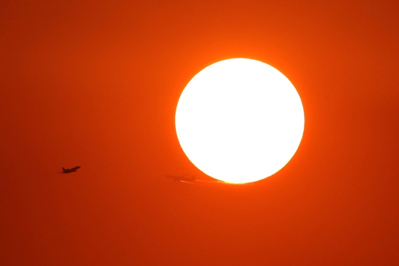 Two planes fly in front of the setting sun in Shanghai