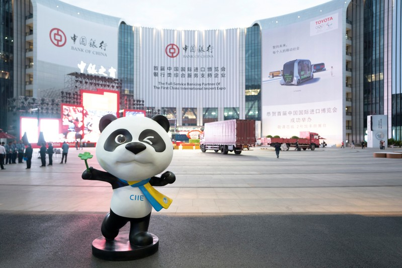 Statue of the China International Import Expo (CIIE)'s mascot is placed in front of a building hanging advertisement of Bank of China, at the venue for the expo in Shanghai