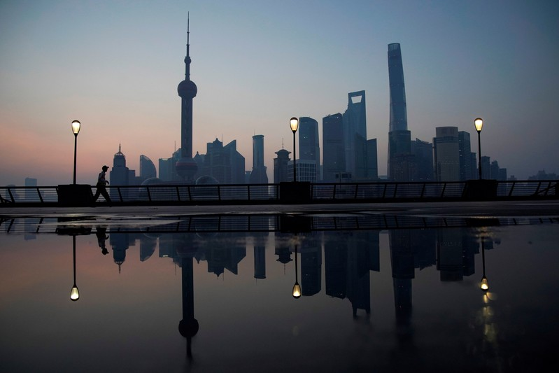A security guard walks on the bund in front of the financial district of Pudong in Shanghai