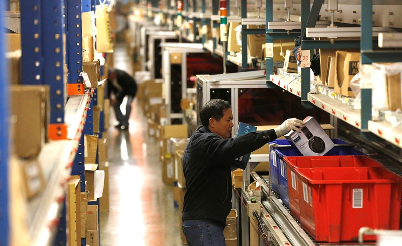 Employees prepare items for shipping at the Newegg warehouse on Cyber Monday in City of Industry