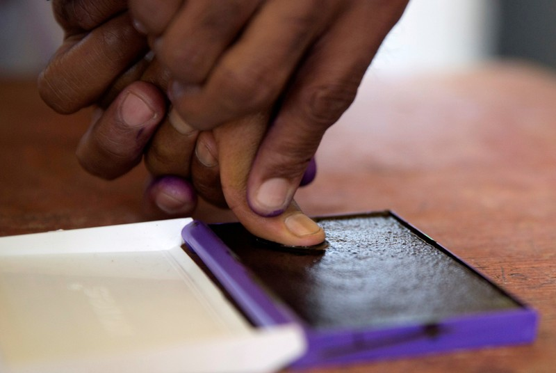 FILE PHOTO: An electoral commission official marks with ink the thumb of a voter after casting his ballot during the presidential election at a polling centre in Analakely, Antananarivo