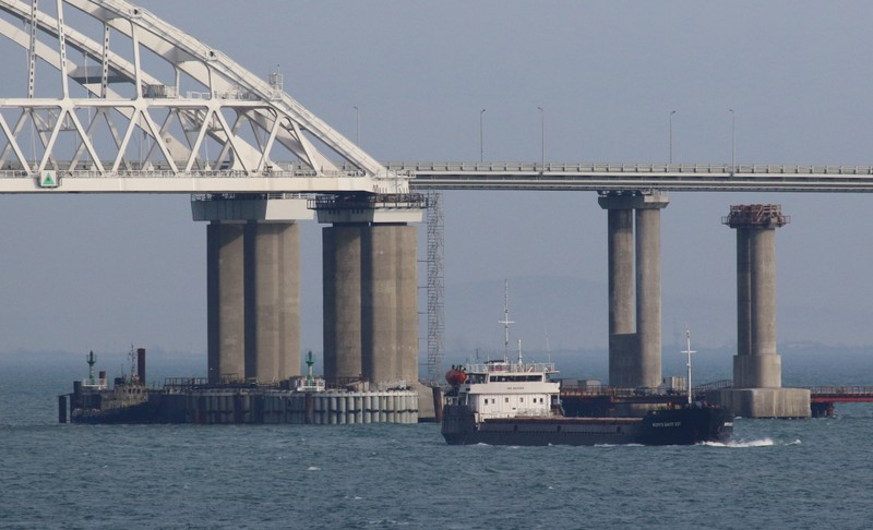 A vessel sails past a bridge connecting the Russian mainland with the Crimean Peninsula across the Kerch Strait