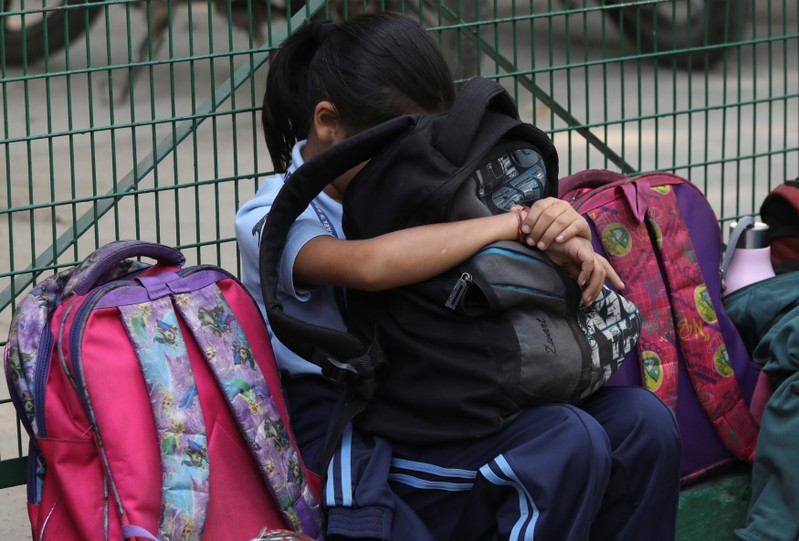 A girl rests her head against a bag outside a school in New Delhi