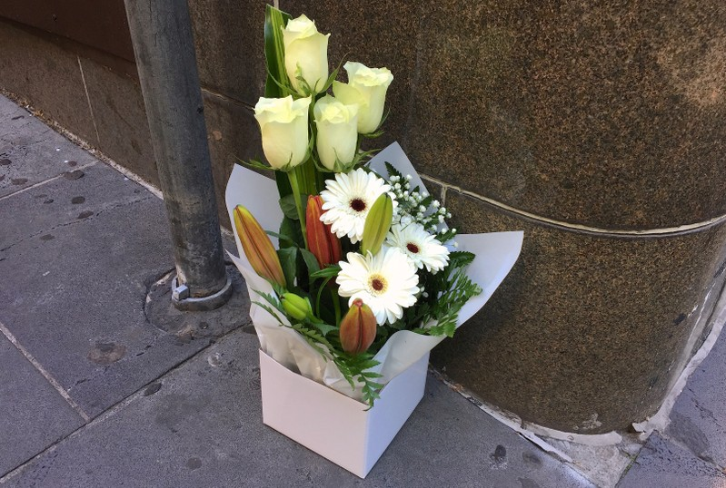 A box of flowers is seen at the site a day after where a man killed one person in what authorities said was a terrorist attack, near the Bourke Street mall in central Melbourne