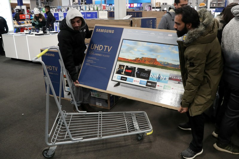 FILE PHOTO: People carry a television inside a Best Buy during a sales event on Thanksgiving day in Westbury, New York