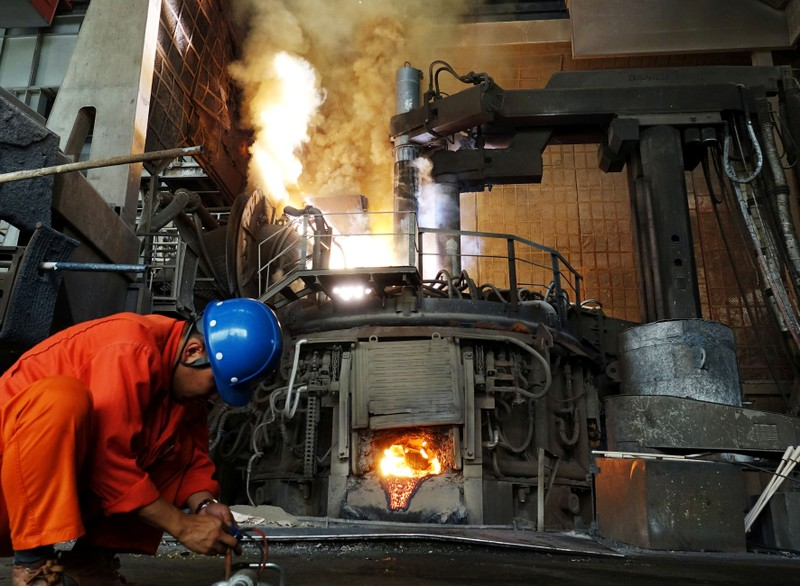 FILE PHOTO: A Man works in front of a furnace at a steel plant of Dalian Special Steel Co Ltd. in Dalian, Liaoning
