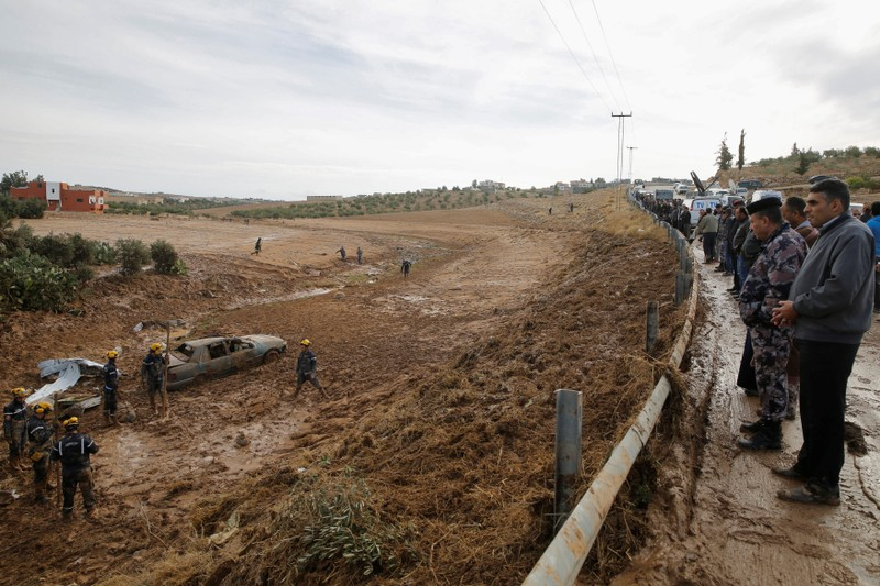 People watch civil defense members as they look for missing persons after rain storms unleashed flash floods, in Madaba city,