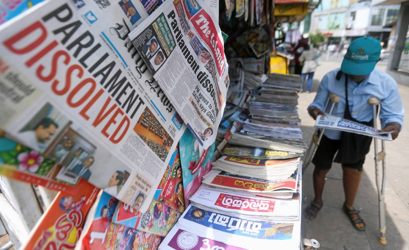 A man reads a newspaper at stall carrying the news of the Sri Lanka's parliament being dissolved, on a main road in Colombo,
