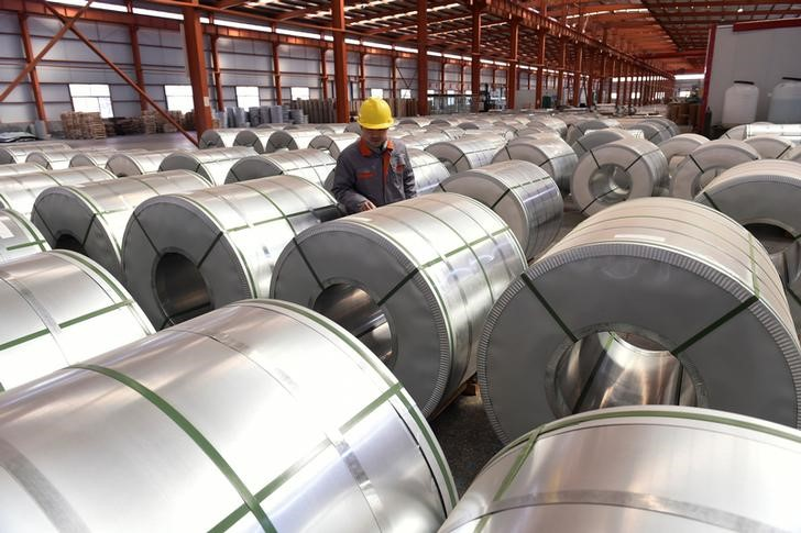 FILE PHOTO - A worker checks aluminium rolls at a warehouse inside an industrial park in Binzhou