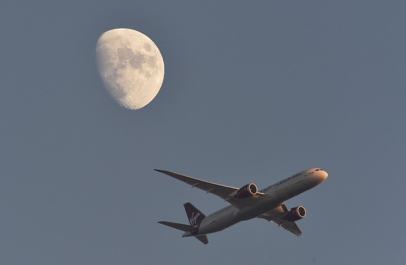 FILE PHOTO: A Virgin Atlantic passenger plane flies in the sky with the moon seen in the background, in London, Britain