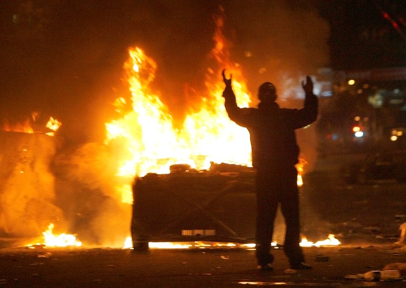 FILE PHOTO: Protester reacts near burning police cars in central Yerevan