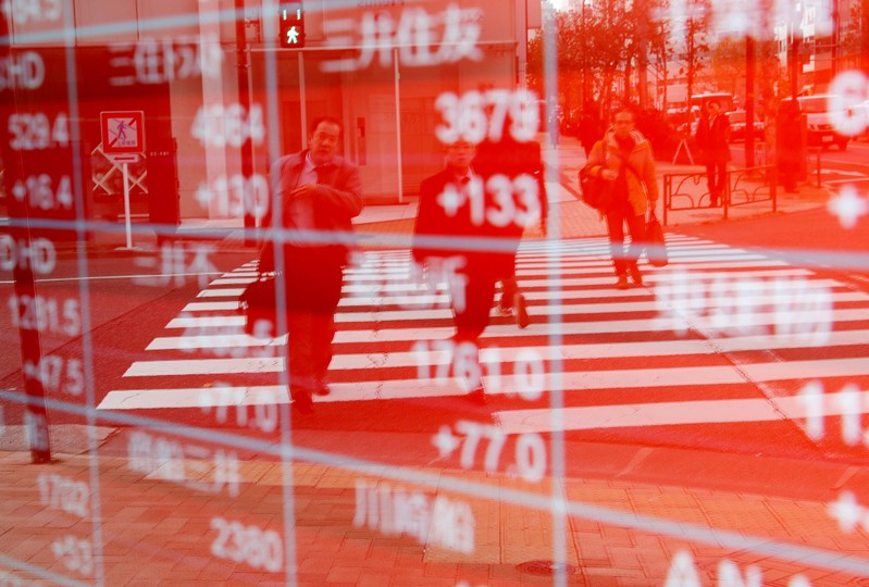 Pedestrians are reflected on an electronic board showing stock prices outside a brokerage in Tokyo