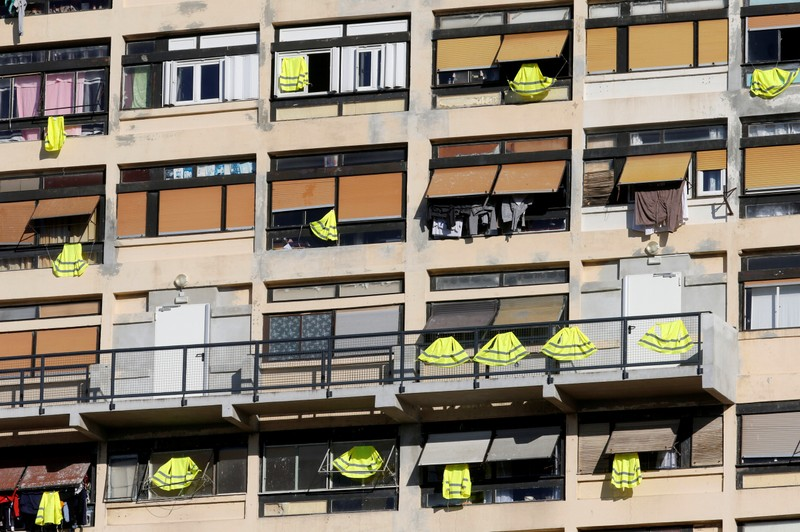 Yellow vests are hung outside windows of an apartment building in support of the