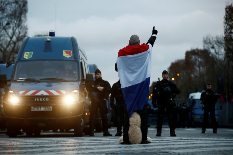 A protester wearing a French flag stand in front of French Gendarmes in place on the Champs-Elysees Avenue during a national day of protest by the