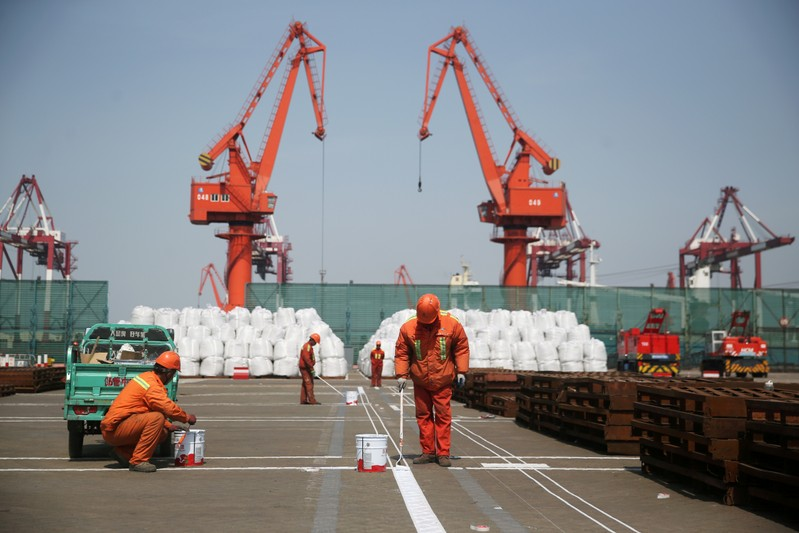 FILE PHOTO: Workers paint the ground at a port in Qingdao