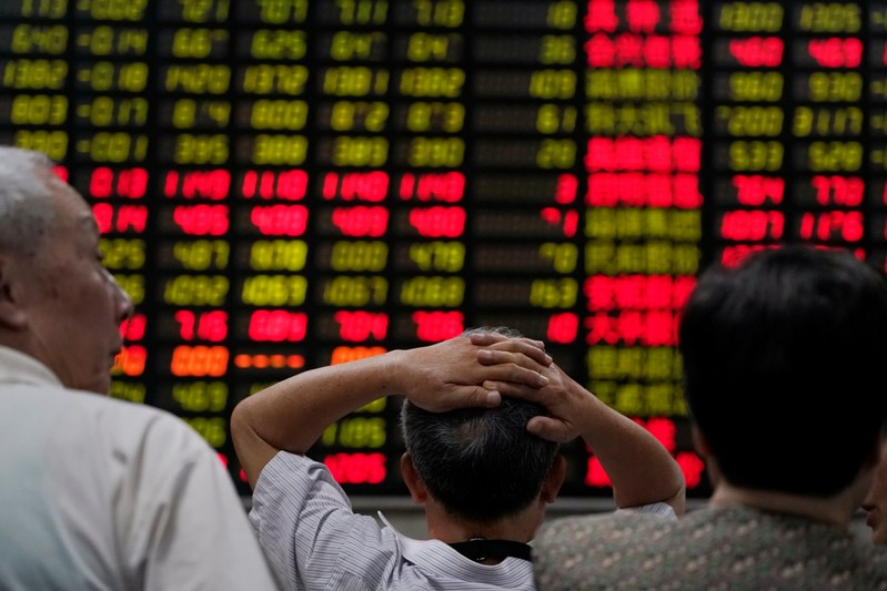 Investors look at an electronic board showing stock information at a brokerage house in Shanghai
